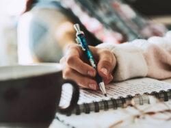 Hand mit Stift schreibt in Notizblock